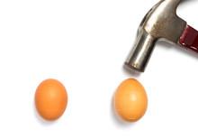 Hammer Is Breaking 2 Eggs On White Background.