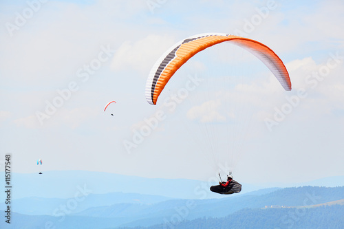 Foto op Canvas Luchtsport Silhouette of paragliders flying in a clear sky over the high mountains in a summer day. Ukrainian Carpathian valley. Extreme sports activity