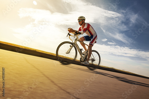 Foto auf Gartenposter Radsport Athlet riding bicycle at sunny day on coastal road, blurred motion