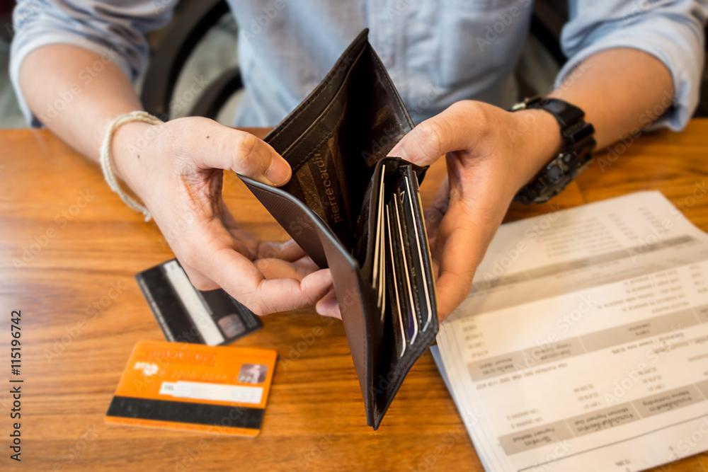 Fototapeta credit card debt - holding an empty wallet.