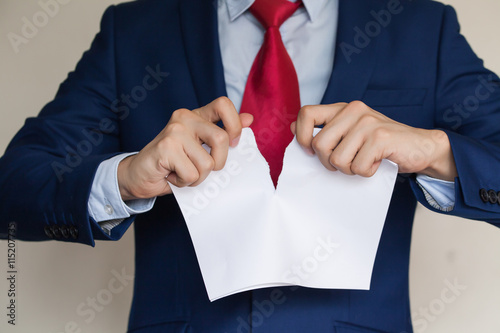 Valokuva  Businessman tearing blank paper apart on white background