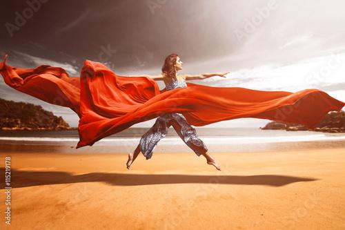 Obrazy na płótnie Canvas Frau springt am Strand zwischen fließenden Stoffen