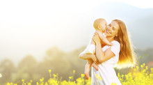 Happy Family Mother And Baby Hugging And Kiss In Summer On Natur