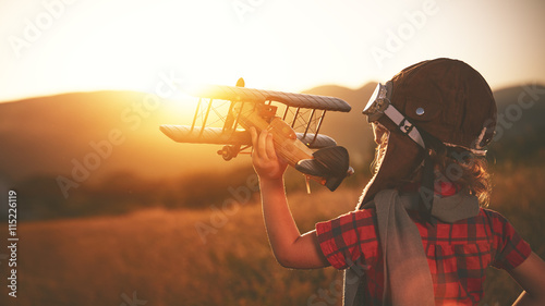 Fotografia  happy child dreams of traveling and playing with an airplane pil