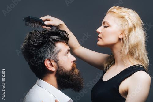 fototapeta na szkło blonde hairdresser combing bearded man