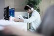 Male designer listening to headphones looking at blueprints at design studio