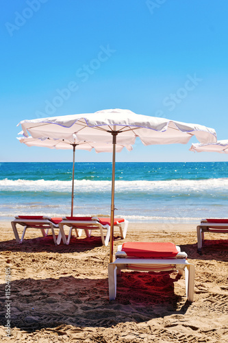 Photo  sunloungers and umbrellas in a quiet beach
