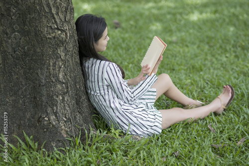 Deurstickers Attractive woman reading a book in the park