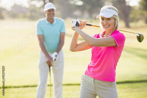 Deurstickers Golf Portrait of confident mature woman carrying golf club by man