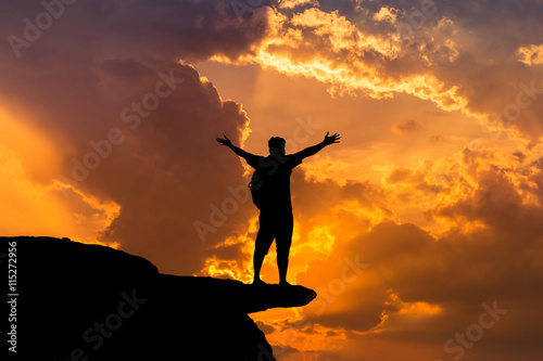 Poster Chasse silhouette man backpacker standing raised up arms achievements successful and celebrate on top mountain in sunset.