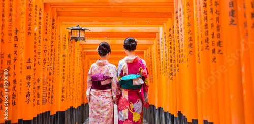 Foto op Plexiglas Kyoto Two geishas among red wooden Tori Gate at Fushimi Inari Shrine in Kyoto, Japan. Selective focus on women wearing traditional japanese kimono.