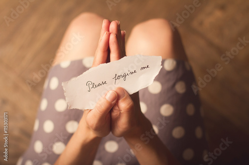 Fotomural  Woman holding a paper note with the text please forgive me