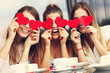 canvas print picture - Three girlfriends holding hearts in cafe