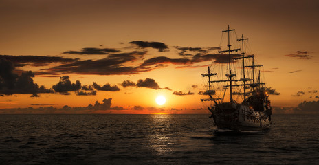 Fototapeta Pirate ship at the open sea at the sunset with copy space