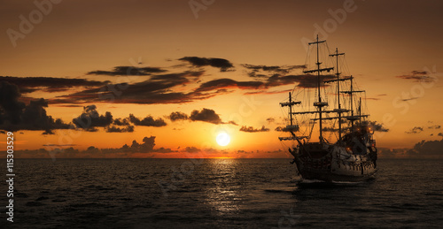 Foto auf Gartenposter Schiff Pirate ship at the open sea at the sunset with copy space