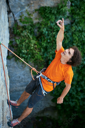 Foto op Aluminium Voetbal male rock climber. rock climber climbs on a rocky wall. man hanging on a rope and shows his hand up