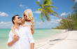happy couple in sunglasses over summer beach