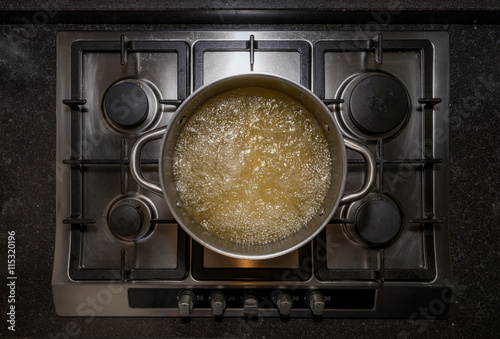 Fotografering  Metal iron aluminum pan on traditional stove cooker boiling water