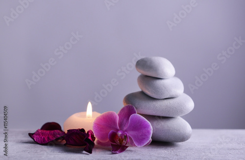 Photo  White spa stones with candle on gray background