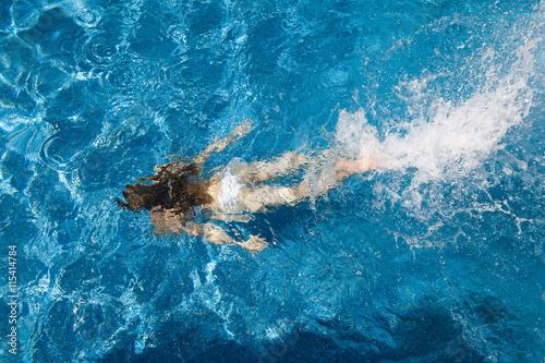 In de dag Dolfijn girl in a white bathing suit under the water in the pool