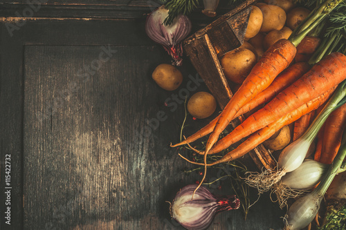Autumn root vegetables cooking ingredients in wooden box on dark rustic background, top view, place for text, top view