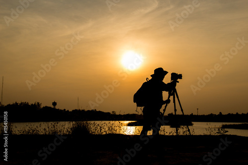 Foto op Canvas Militair silhouette of photographer a lake on sunset.
