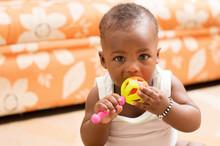 Portrait D'un Bébé Assis Portant à La Bouche Son Jouet
