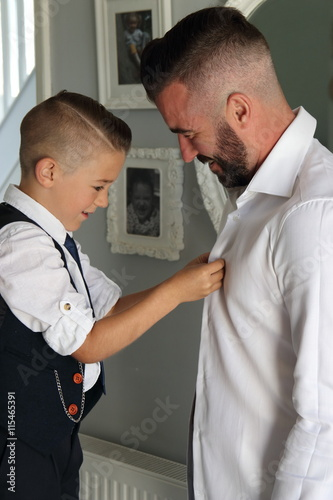 A Young Boy Dressing His Father On Wedding Day As Part Of Best Man