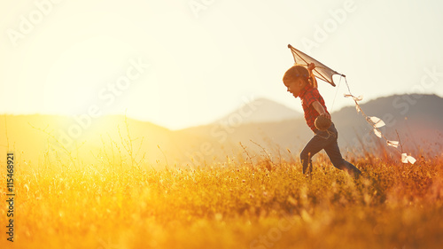 Obraz na plátne happy child girl with a kite running on meadow in summer
