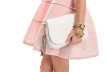 Girl's Hand Holds White Bag. Small Classic Watch And Bracelets. New Leather Handbag. Salmon Dress And Trendy Accessories.
