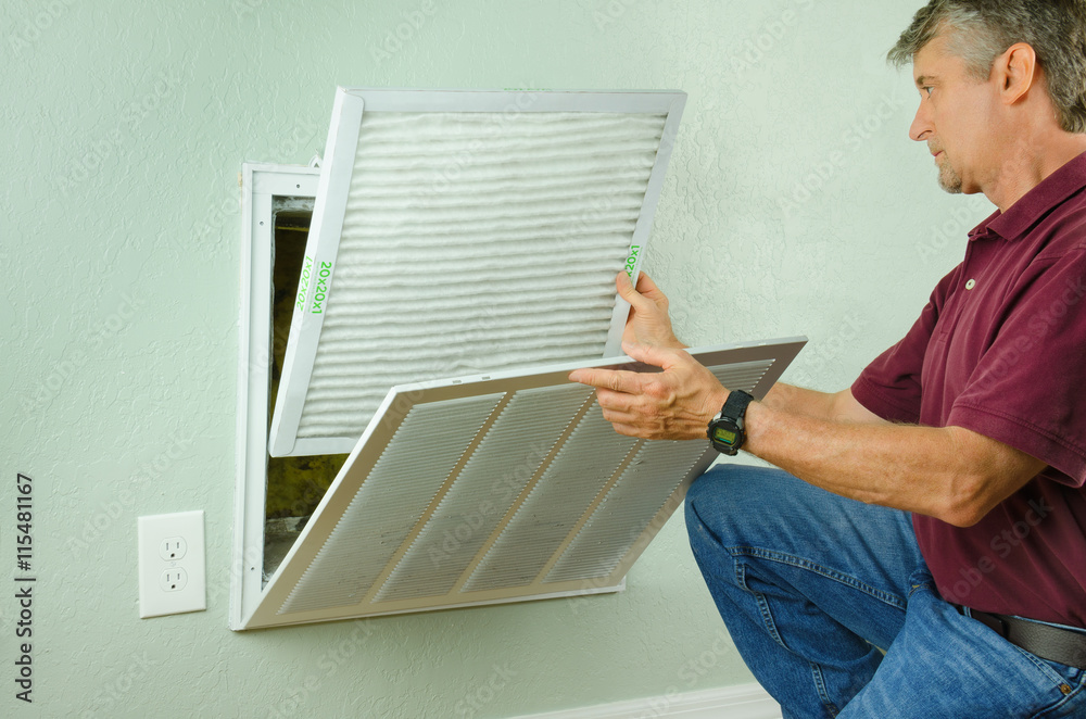 Fototapeta Professional repair service man or diy home owner a clean new air filter on a house air conditioner which is an important part of preventive maintenance.