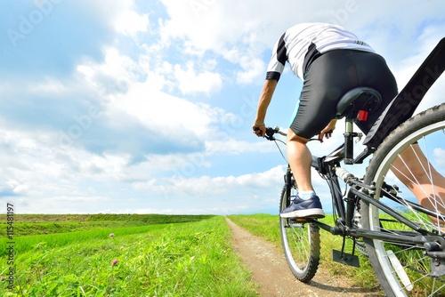 Fotografie, Obraz  大 空 と 田園 の 風景 を マ ウ ン テ ン バ イ ク で 走 る