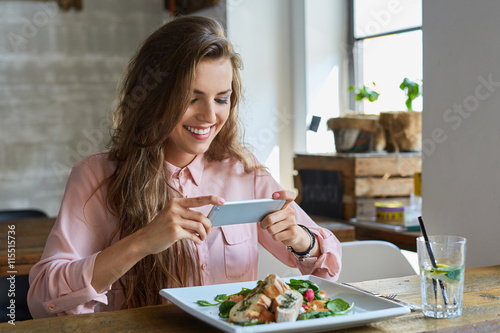 Photo  Female blogger photographing lunch in restaurant with her phone