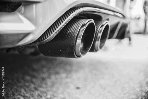 Double exhaust pipes of a modern sports car, black and white