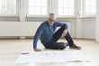Man looking at construction plan in empty apartment