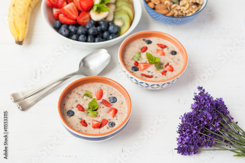 Aluminium Prints Food Vegan fruit and berry smoothie breakfast, topped with blueberries, strawberries and mint, seved with fruits, berries and nuts, selective focus