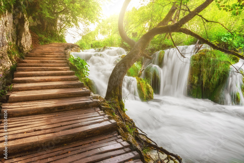 Plitvice Lakes National Park, tourist route on the wooden flooring along the waterfall, Croatia, nature sunny background