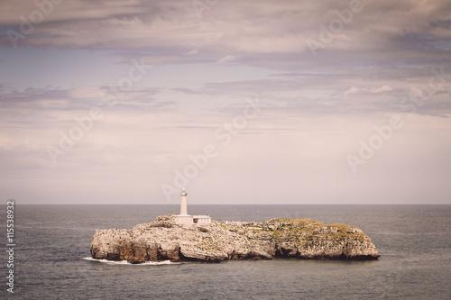 Poster Vuurtoren Lighthouse over rocks on an island, Spain