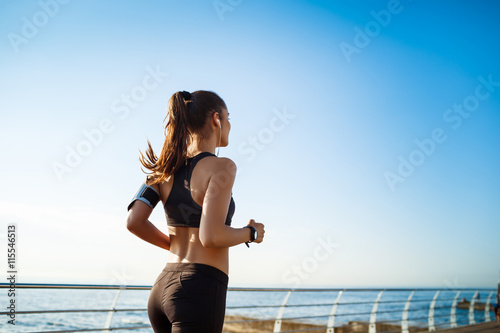 Foto op Canvas Jogging Picture of young attractive fitness girl jogging with sea on background