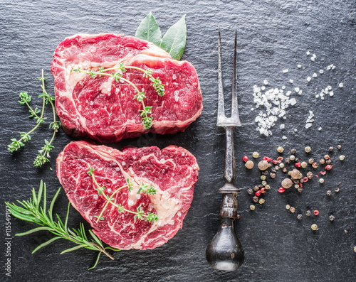 obraz lub plakat Rib eye steaks with spices on the black background.