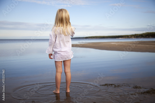 Sweden, Medelpad, Juniskarr, Blonde girl (6-7) standing in water