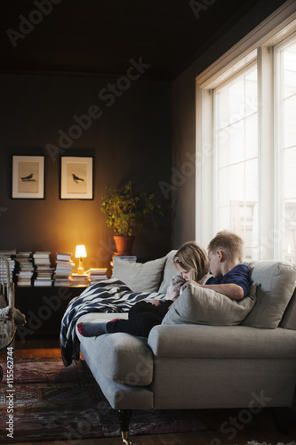 Denmark, Boy (8-9) and girl (4-5) sitting on sofa in living room Poster