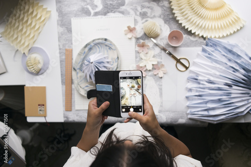 Sweden, Woman photographing origami on table Poster