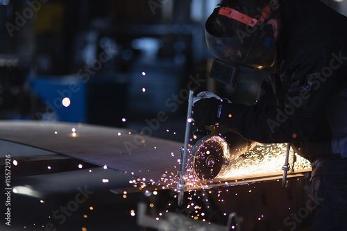 Sweden, Young man cutting metal in workshop