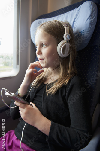 Denmark, Girl (6-7) sitting on train and listening to music
