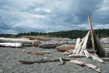 Driftwood Teepee On A Sandy Beach With Stormy Sky