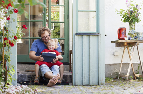 Sweden, Skane, Mossby, Daughter with father sitting on stone step and holding tablet pc