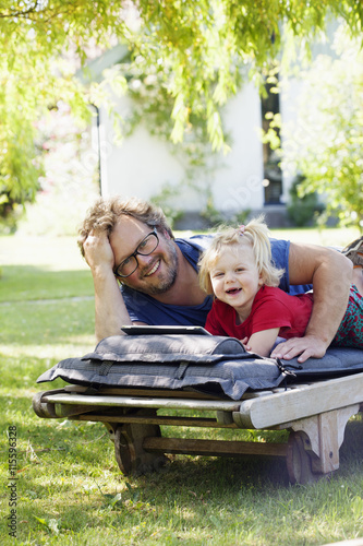 Sweden, Skane, Mossby, Portrait of daughter with father lying on deckchair and using tablet pc
