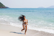 Happy woman running to the sea on white sand beach