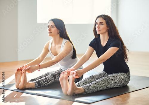 Foto  Zwei junge Frauen, die Yoga Asana tut Zehen mit konkaven zurückhalten
